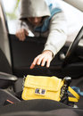 Thief stealing bag from the car transportation crime and ownership concept Royalty Free Stock Photo