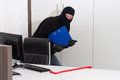 Thief stealing company info a burglar is robbing knowledge from a Royalty Free Stock Photo