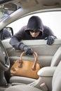 Thief stealing handbag from car at parking lot Stock Image