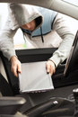 Thief stealing laptop from the car transportation crime and ownership concept Stock Photo