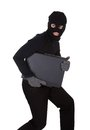 Thief stealing a laptop computer dressed in black and wearing balaclava and making furtive escape isolated on white Royalty Free Stock Image