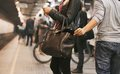 Thief stealing wallet at the subway station young woman using mobile phone being robbed by a pickpocket pickpocketing Stock Photos