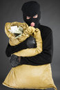 Thief with stolen goods front view of frustrated man in black balaclava holding a money bag while standing isolated on grey Royalty Free Stock Photo