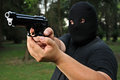 Thief threatening with a gun masked Royalty Free Stock Photos