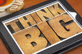 Think big on digital tablet motivational phrase in letterpress wood type a with a cup of tea Royalty Free Stock Images