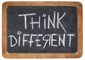 Think different on blackboard motivational phrase white chalk handwriting a vintage slate Stock Image