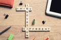 Think different concept of crossword puzzle on wooden surface or Royalty Free Stock Photo