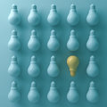 Think different concept , One yellow light bulb stand out from unlit green incandescent lightbulbs with shade and shadow