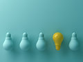 Think different concept , One yellow light bulb standing out from the unlit green incandescent lightbulbs