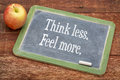 Think less feel more motivational words on a slate blackboard against red barn wood Stock Photos