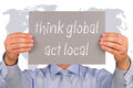Think global and act local businessman holding a sign with a world map in the background Royalty Free Stock Photo