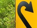 Think green - U-turn roadsign in lush vegetation Royalty Free Stock Photo
