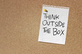 Think outside the box concept image of a note paper with words written on it over cork board background Royalty Free Stock Photo