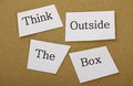 Think outside the box in cut out text on a background of brown cardboard well known phase applies to creative thinking and Royalty Free Stock Photography
