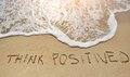 Think positive written on sand beach - positive thinking concept Royalty Free Stock Photo