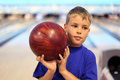 Thinking boy holds ball in bowling Royalty Free Stock Photo