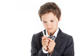 Thinking boy in white shirt tie and jacket holding two chess pieces in each hand having a thoughtful look Stock Images