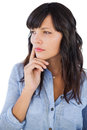 Thinking brunette with finger on her face looking away white background Stock Images