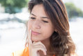 Thinking caucasian woman in a orange shirt Royalty Free Stock Photo