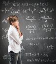 Thinking child with mathematical problem in the blackboard Stock Photo