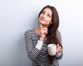 Thinking concerned young woman looking up with cup of coffee Royalty Free Stock Photo