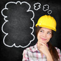 Thinking construction worker girl on chalkboard young female architect engineer surveyor wearing hardhat blackboard with hand to Royalty Free Stock Photography