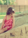 Thinking cute kid girl looking on big stone outdoors background Royalty Free Stock Photography
