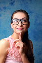 Thinking cute woman in glasses looking on blue background Royalty Free Stock Images