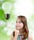 Thinking girl looking at the bulb Royalty Free Stock Images