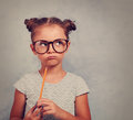 Thinking grimacing kid girl in glasses looking and holding pencil in hand on blue background with empty copy space. Toned vintage