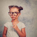 Thinking grimacing kid girl in glasses looking up and have an id Royalty Free Stock Photo