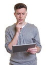 Thinking guy in a grey shirt working with tablet computer Royalty Free Stock Photo