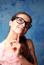 Thinking happy girl in glasses looking up on blue background Royalty Free Stock Image
