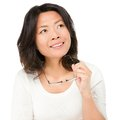 Thinking mature asian woman Royalty Free Stock Images
