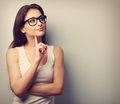 Thinking professional woman in glasses looking with finger under