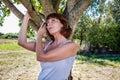 Thinking 50s woman under tree for metaphor of nostalgia