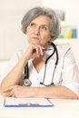 Thinking senior doctor woman sitting at table Stock Image