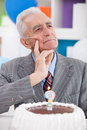 Thinking senior man with birthday cake how old is Royalty Free Stock Images