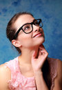 Thinking student girl in glasses looking up on blue background Royalty Free Stock Photo
