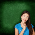 Thinking woman student or teacher with blackboard standing contemplative and pensive looking up to the side at empty green Stock Photo