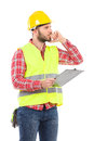 Thinking worker with a clipboard engineer in yellow helmet and lime waistcoat holding and three quarter length studio shot Royalty Free Stock Photos