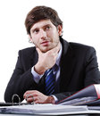 Thinking young businessman sitting behind the desk Stock Photos