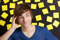 Thinking young student in front of a board full of yellow notes Royalty Free Stock Photos