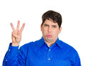 Third place loser closeup portrait annoyed young sad man looking at you holding number three gesture by hand displeased he came in Royalty Free Stock Photo