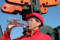 Thirst oil worker quench with water next to pump jack Royalty Free Stock Image