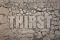 Thirst the word written on the dried ground Stock Photos
