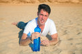 Thirsty desert traveler red faced with sun heat with a bottle of cold water Royalty Free Stock Photos