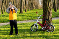 Thirsty little boy cyclist drinking bottled water in a wooded rural park with his bicycle leaning against a tree trunk nearby Stock Images