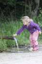 Thirsty little girl stopping at a headspring Stock Images