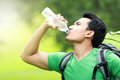 Thirsty man drinking a bottle of water hiking concept having break Royalty Free Stock Photography